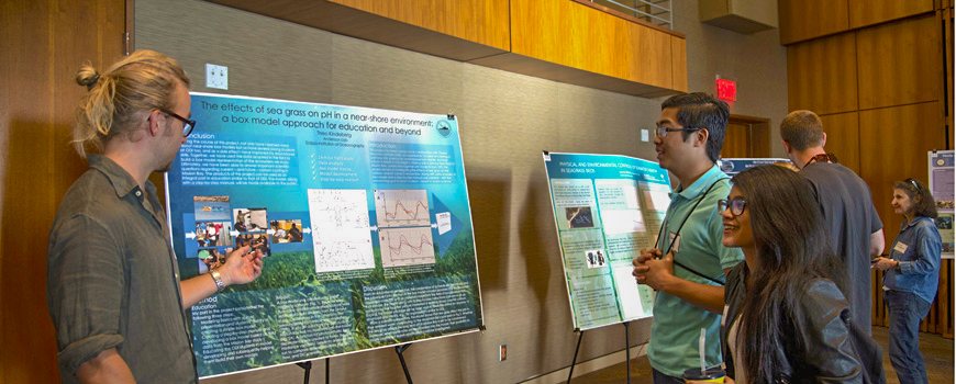 A student shares his research poster at an event.