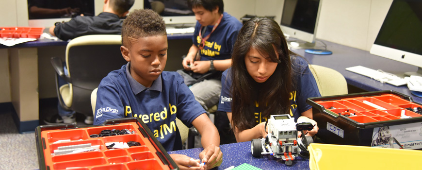 Students build robots in a classroom.