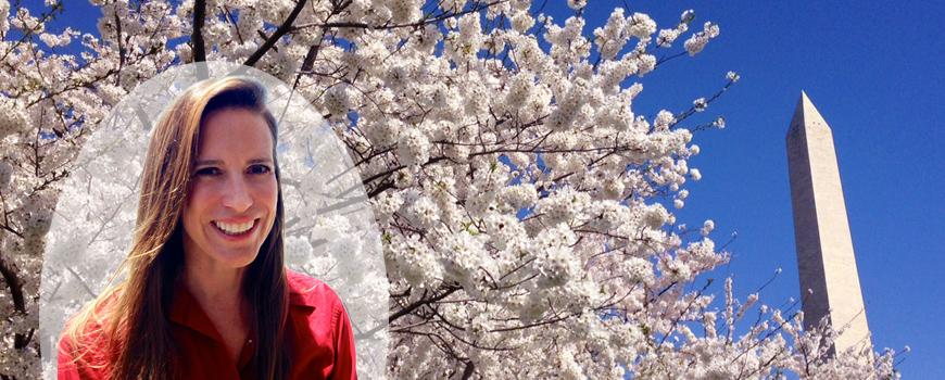 A woman smiles near a cherry blossom tree.