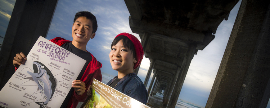 Two students under a pier hold educational posters.