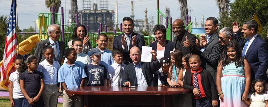 Gov. Brown signs SB 1383 into law flanked by Scripps researcher Ramanathan (back row, left) and others. Photo: CA State Sen.
