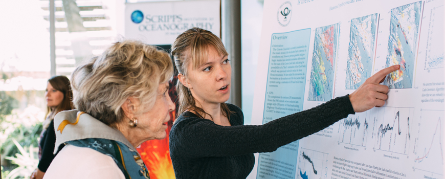 Two women look at a research poster.