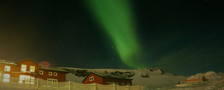 The Northern Lights, or aurora borealis, illuminate Arctic station housing Scripps researchers in Greenland. Photo: Jacob Morgan