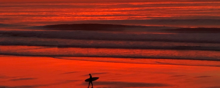 A surfer emerges from the ocean at La Jolla Shores amid a colorful sunset, Jan. 8, 2019. Photo: Brittany Hook
