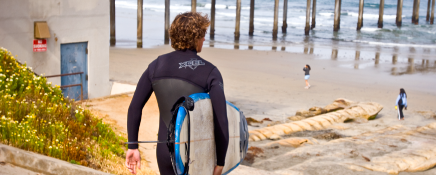 A student in a wetsuit carries a surfboard down to La Jolla Shores.