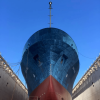 Red and blue research vessel sitting in drydock